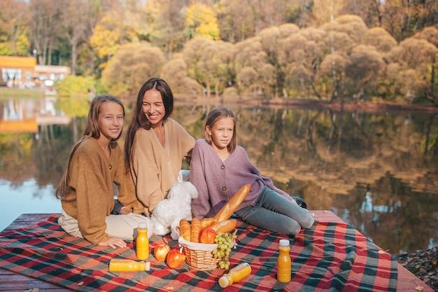 Mutter und kinder im herbst beim picknick auf dem see