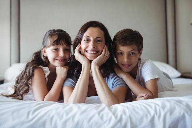 Mutter und kinder liegen im schlafzimmer auf dem bett