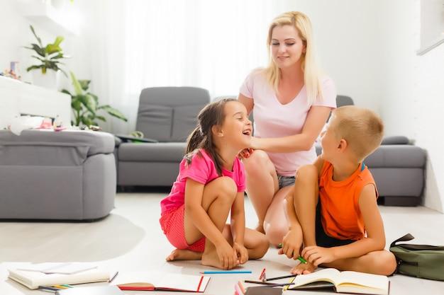 Mutter und kinder machen hausaufgaben auf dem boden