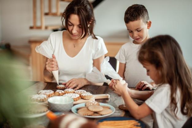 Mutter und kinder schmücken weihnachtslebkuchen zu hause. ein junge und ein mädchen malen mit kornetten mit