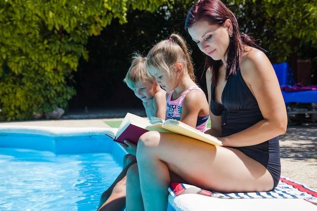 Mutter und kinder sitzen am pool