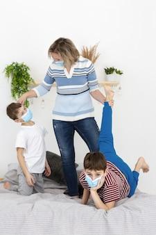 Mutter und kinder spielen zusammen, während sie medizinische masken tragen