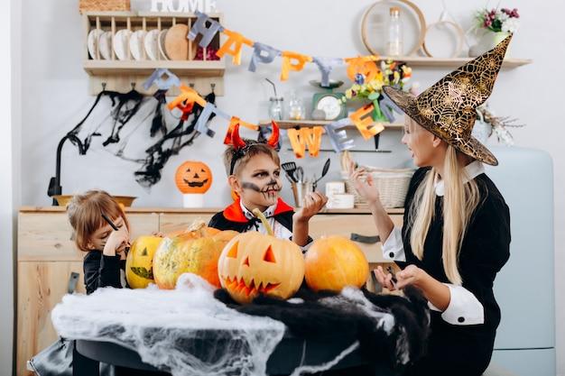 Mutter und kinder unterhalten sich und haben lustige stunden zu hause. halloween