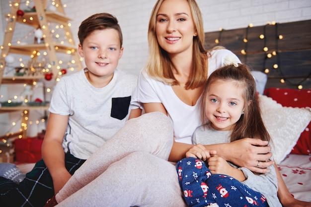 Mutter und kinder verbringen weihnachtsmorgen im bett