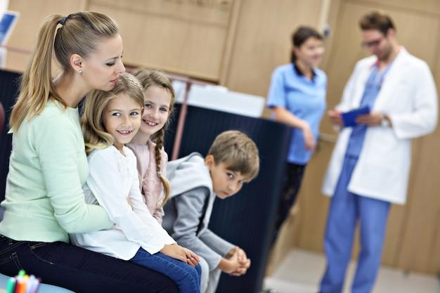 Mutter und kinder warten vor dem registrierungsschalter im krankenhaus