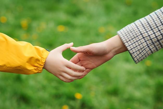 Mutter- und kinderhände, die einander erreichen. unterstützung, hilfe und vertrauen. eltern halten die hand eines kindes auf einem spaziergang. kinder- und mutterhände auf naturhintergrund. liebe, beziehung und teamwork in der familie