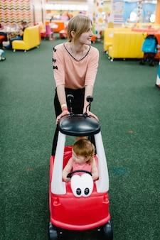 Mutter und kleine kinder das mädchen fährt auf einem roten wunderschönen großen auto auf der straße. nahaufnahme. das baby fährt auto und spielt auf einer geburtstagsfeier in einem kinderspielzimmer.