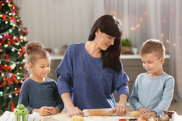 Mutter und kleine kinder machen weihnachtsplätzchen in der küche