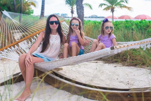 Mutter und kleine mädchen, die in der hängematte am tropischen erholungsort sich entspannen