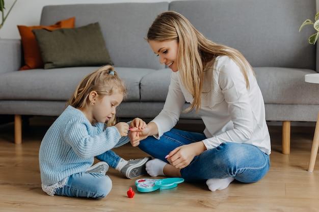 Mutter und kleine tochter bemalen ihre nägel mit spielzeugnagellack