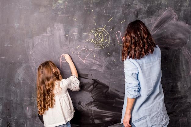 Mutter und kleine tochter, die auf tafel zeichnen