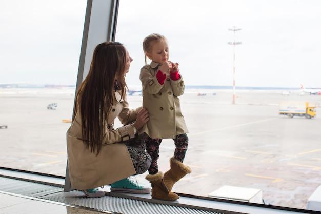 Mutter und kleine tochter, die heraus das fenster flughafenabfertigungsgebäude betrachten