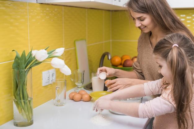 Mutter und kleine tochter, die in der küche kochen