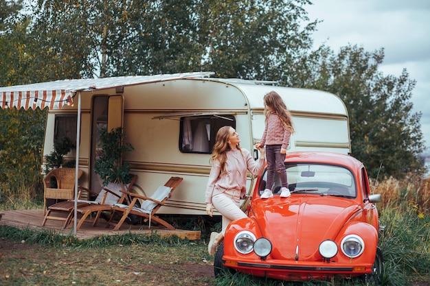 Mutter und kleine tochter, die spaß in der landschaft auf reisemobilferien mit rotem retro- auto sich entspannen und haben