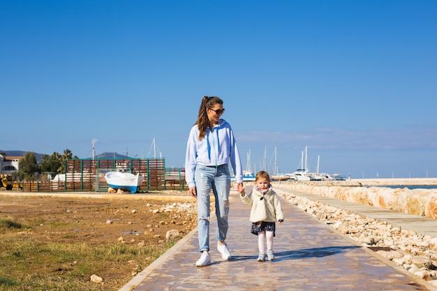 Mutter und kleine tochter gehen am strand spazieren.