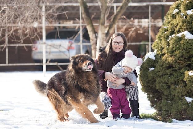 Mutter und kleine tochter gehen an einem wintertag spazieren und spielen mit ihrem hund