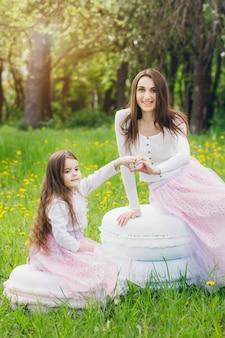 Mutter und kleine tochter gehen im frühling blühenden apfel spazieren
