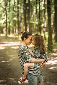 Mutter und kleine tochter gehen im wald spazieren