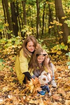 Mutter und kleine tochter gehen mit ihrem jack-russell-terrier-hund im herbstwetter stilvoll