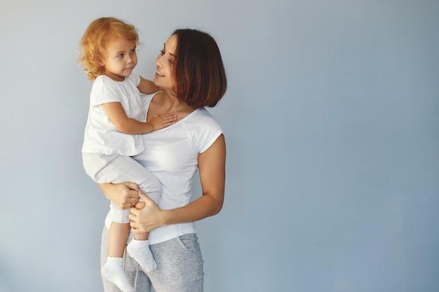 Mutter und kleine tochter haben spaß auf einem blauen hintergrund