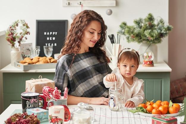 Mutter und kleine tochter in der küche dekoriert für das neue jahr und weihnachten