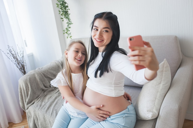 Mutter und kleine tochter machen zusammen selfie.