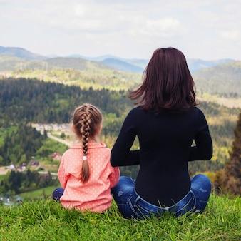 Mutter und kleine tochter meditieren auf dem gipfel des berges