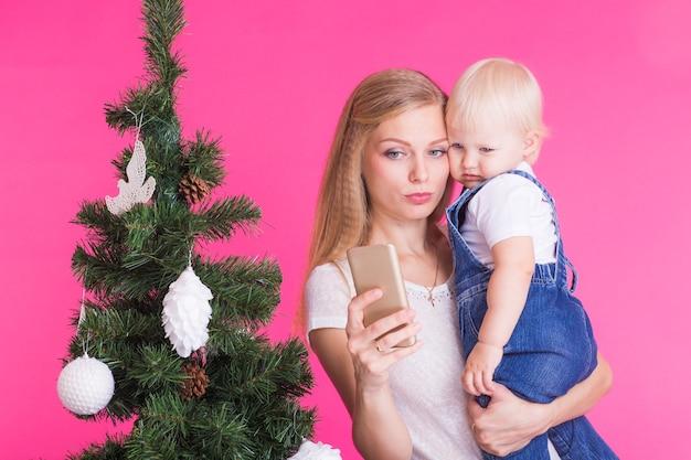 Mutter und kleine tochter nehmen ein selfie nahe weihnachtsbaum