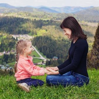 Mutter und kleine tochter sitzen oben auf dem berg.