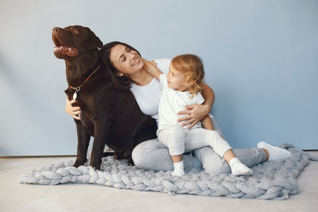 Mutter und kleine tochter spielen mit hund zu hause