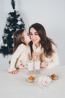 Mutter und kleine tochter trinken kakao mit marshmallows