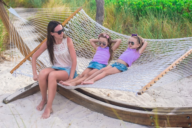 Mutter und kleine töchter, die in den sommerferien in der hängematte sich entspannen