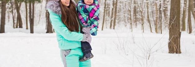 Mutter und kleiner kleinkind, die im winterwald spazieren und spaß mit schnee haben. familie, die den winter genießt. kind und frau, die draußen fallenden schnee beobachten. winter-, weihnachts- und lifestyle-konzept.