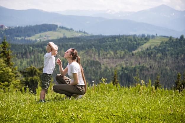Mutter und kleiner sohn blasen löwenzahn nadelwald und berge. mutterschaft und freundschaft