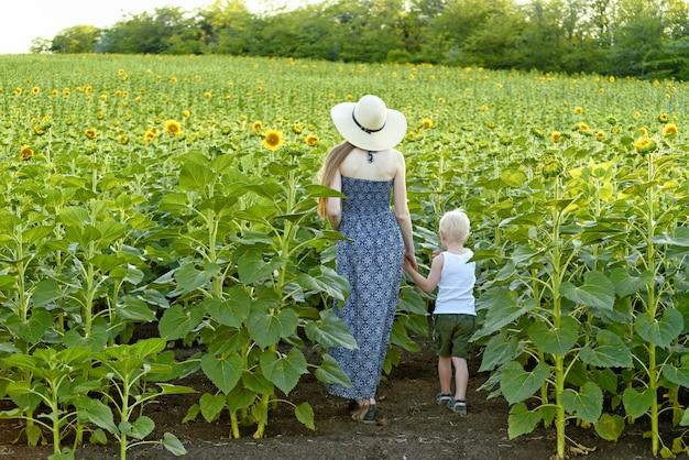 Mutter und kleiner sohn, die auf dem gebiet von sonnenblumen gehen