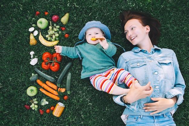 Mutter und kleines baby auf grünem gras mit rahmen aus frischem obst und gemüsegesunde ernährung