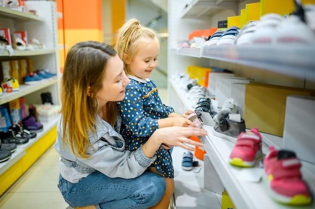 Mutter und kleines baby, die auf schuhen im kinderladen schauen