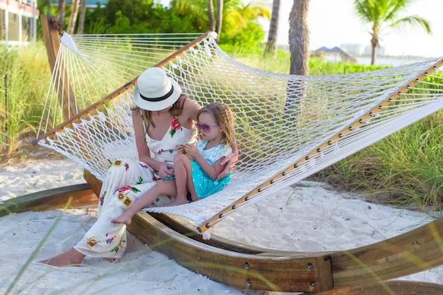 Mutter und kleines mädchen, die in der hängematte am tropischen erholungsort sich entspannen