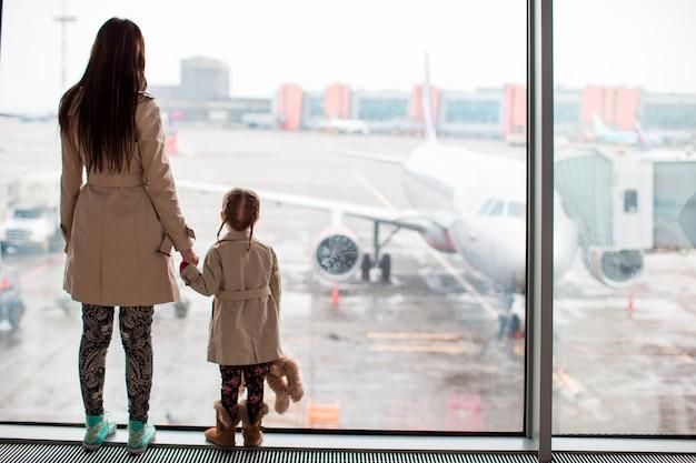 Mutter und kleines mädchen im flughafenwartebrett