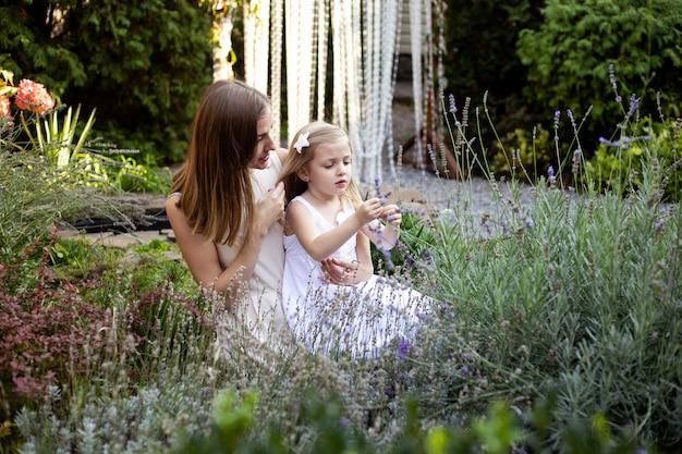 Mutter und kleines mädchen in lavander umarmen sich und haben spaß im freien in der natur