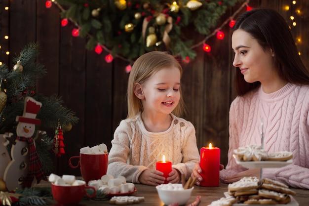 Mutter und kleines mädchen mit weihnachtsplätzchen zu hause