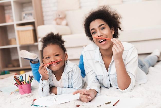 Mutter und kleines mulattin liegen mit filzstiften auf dem boden.