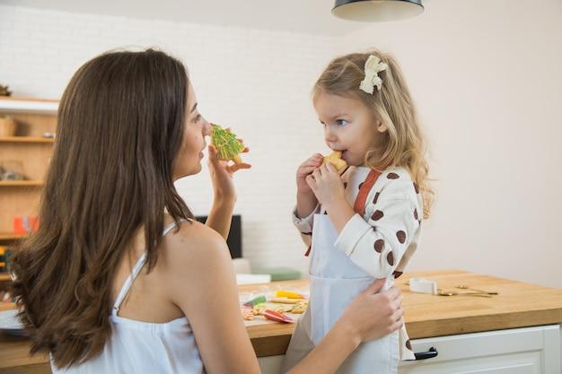 Mutter und kleinkindtochter backen lebkuchenplätzchen für weihnachten. dekorieren von hausgemachten keksen für die winterferien.