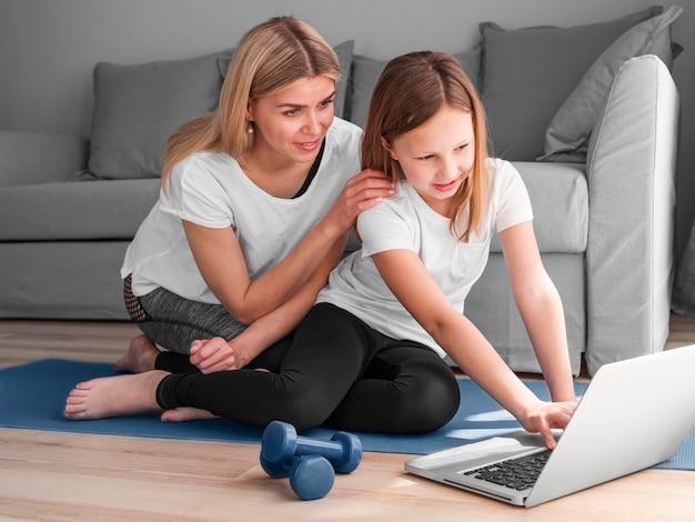 Mutter und mädchen auf der suche nach sportvideos
