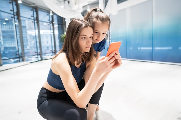 Mutter und mädchen, die telefon im fitnessstudio zum ansehen des videos verwenden