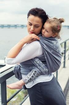 Mutter und mädchen gewickelt in graue schlinge zurück am stadtflusshintergrund, baby tragend
