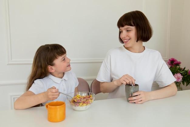 Mutter und mädchen mit mittlerer aufnahme am tisch