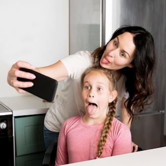 Mutter und mädchen nehmen selfie