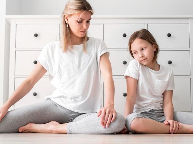 Mutter und mädchen sport üben stretch