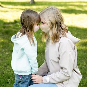 Mutter und mädchen tragen medizinische maske